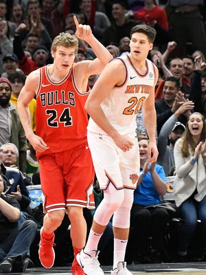 Chicago Bulls forward Lauri Markkanen (24) reacts after dunking  the ball as New York Knicks forward Doug McDermott (20) looks on during the second half at United Center on Wednesday,. Dec. 27, 2017.