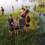 Spectators gather in the marsh in anticipation of the 90th annual Pony Swim on Chincoteague, Virginia on Wednesday, July 29, 2015.