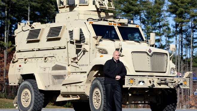 Warren County Undersheriff Shawn Lamouree poses in front the department's mine resistant ambush protected vehicle, or MRAP, on Wednesday, Nov. 13, 2013, in Queensbury, N.Y. The hulking vehicles, built for about $500,000 each at the height of the war, are among the biggest pieces of equipment that the Defense Department is giving to law enforcement agencies under a national military surplus program.