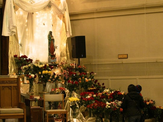 Parishioners lay roses at St. Celement in Sheboygan
