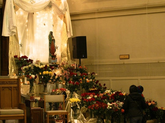 Parishioners lay roses at St. Celement in Sheboygan in celebration of Our Lady of Guadalupe during a midnight mass Saturday morning.