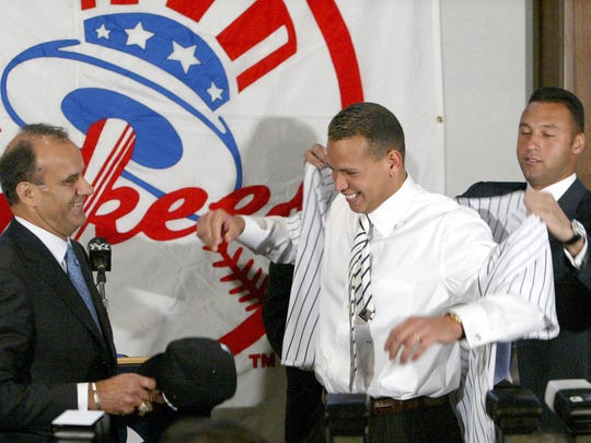 Yankees shortstop Derek Jeter, right, helps new Yankees third baseman Alex Rodriguez try on his new pinstripe uniform as Yankees manager Joe Torre looks on during a news conference at Yankee Stadium in 2004.