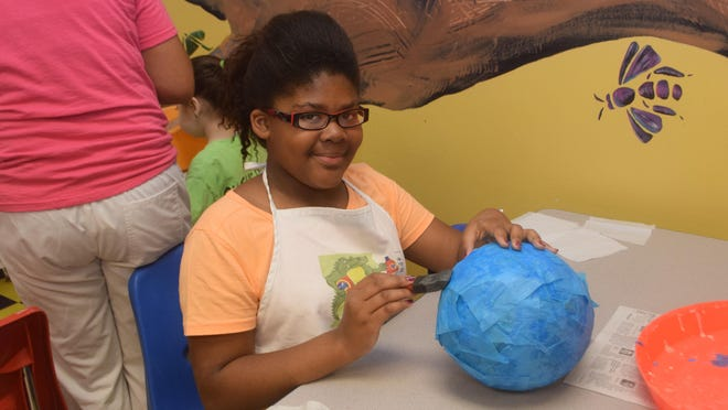 Franjone' Price makes a papier-mache birdhouse Wednesday during a summer camp held at the T.R.E.E. House Children's Museum.