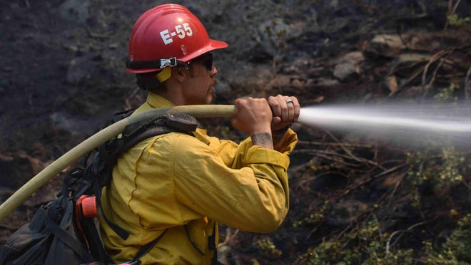 U.S. Forest Service firefighter from Los Padres National Forest soaks a hillside off of Highway 38 near Big Bear on Friday.