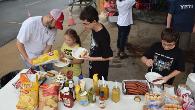 Erik Larson (far left) prepares hot dog plates for his children Alexis Larson and David Larson and Jack Blair (far right) gets some hot dogs at the annual Burnt Weenie Festival held Saturday at the Tamp & Grind Coffee House in downtown Alexandria.