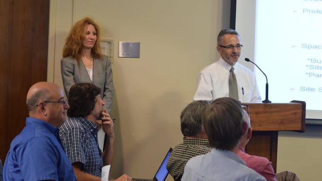 Sandra Rybicki (far left, standing), real estate specialist with the U.S. Postal Service, and Mike Llewellyn, regional portfolio manger for the U.S. General Services Administration, speak at a public hearing concerning the relocation of the Murray Street Postal Station.