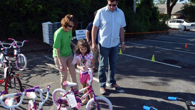 """Lisa Allemand (left) of the Laborde Earles Law Firm helps Abby Ledger (center) pick out her bike. With Abby is her brother Alex Snyder (right) who brought her to the """"Bike It Forward"""" giveaway at Alexandria Senior High School on Friday. Laborde Earles Law Firm gave away 200 bikes and helmets in Alexandria and Lafayette."""