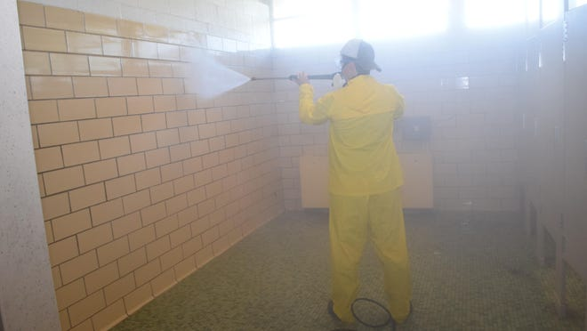 """Reldon Owens, a member of the Parent Teacher Organization of Phoenix Magnet Elementary School, pressure washes the boys' bathroom at the school. Members of the Parent Teacher Organization gathered at Phoenix on Saturday to clean, paint and landscape. """"We'll have other events like this throughout the year,"""" Principal John Grimes said. He said the PTO gives parents a chance to get involved with the school and beautify the campus."""