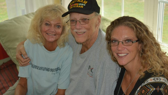 Wayne Moore, center, sits with his wife, Holly, and daughter, Tracy Moore Warren, at his and Holly's retirement home near Lewes.