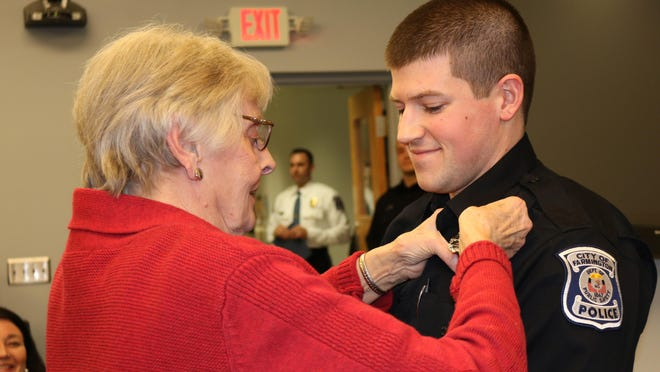 Officer Jacob Cote, who recently joined the Farmington Public Safety Department, has his badge pinned on by his grandmother, Judy Cote, during the Jan. 19 city council meeting.
