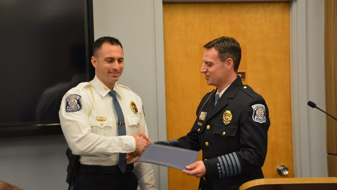 Public Safety Director Frank Demers congratulates Cmdr. Andrew Morche on his promotion.