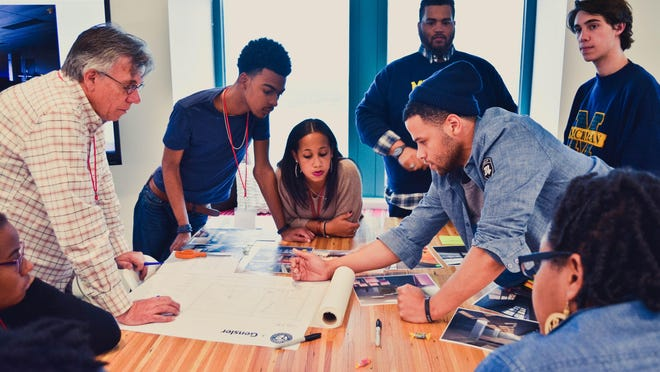 FATE students and mentors Cyan Sims (from lower left), Dale Boomer, DaJuan Thomas, LeAuna Brown, David Merritt (leaning across table), Michael Chrzan, Harry Champion, and Ashley Jordan, work with Gensler, an American design and architecture firm, to help design the new Merit/FATE Detroit location, which will open in 2016.