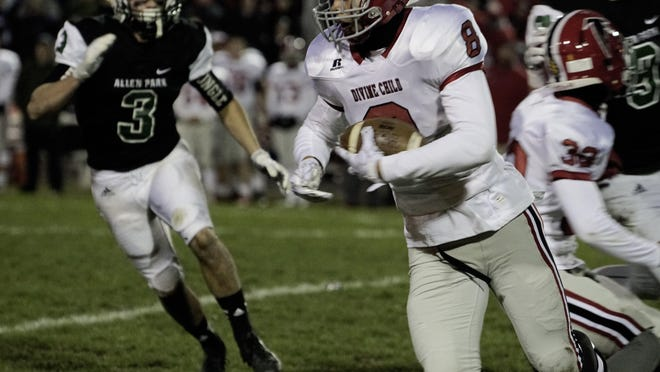 Divine Child defensive back Evan Latham goes for yardage after intercepting a pass against Allen Park in a regional championship game Friday.