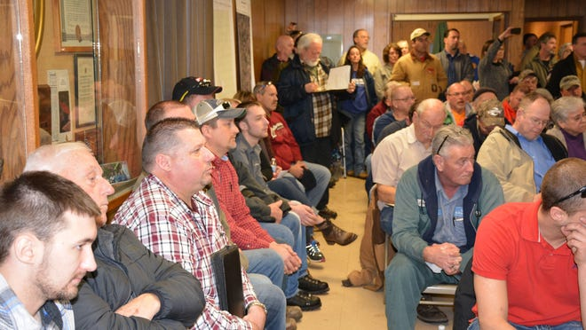 Randy Schmidt, in red plaid shirt, one of the owners of S & S Jerseyland Dairy LLC, sits with family and supporters during the hearing about a permit for the farm on March 2, 2017, in Forestville.