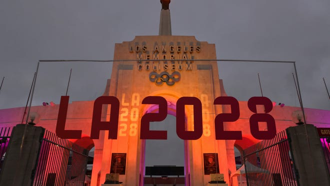 An LA 2028 sign is seen in front of a blazing Olympic cauldron at the Los Angeles Memorial Coliseum in September 2017, when the city was named host for the 2028 Olympics. Some people are calling for city leaders to give up hosting privileges.