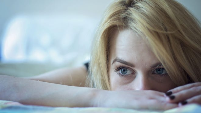 Beautiful young blond hair woman laying in bed and thinking