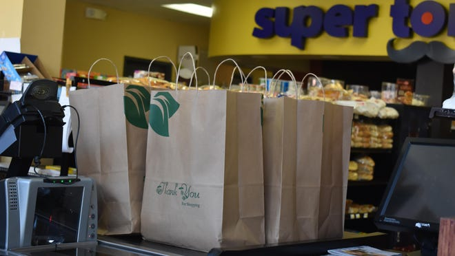 Bags of groceries containing necessities like eggs, juice andbread sit at a check-out in Garcia Supermarket in Middletown.