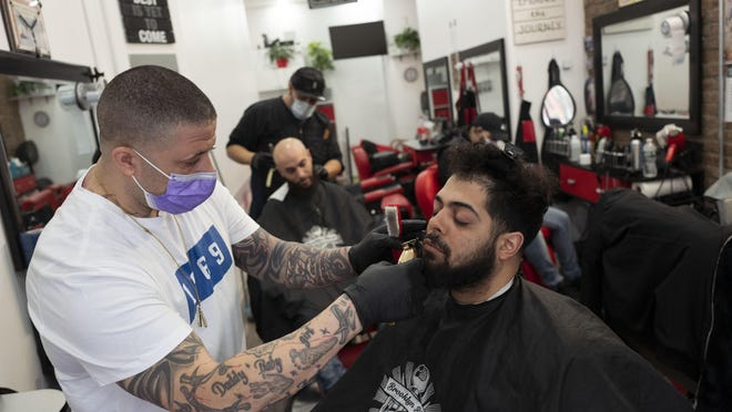 Jose Cepeda, left, trims David Rosario's hair at Brooklyn Blends barber shop, Friday, March 20, 2020 in New York. Business is down since the arrival of the coronavirus, according to Cepeda.