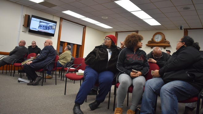 At Tuesday evening's Middletown Common Council meeting, Newburgh residents Juanita King, right, and daughter Deonne Chambers, center, watch footage of an incident that took place Friday outside a Middletown-Newburgh varsity basketball game.