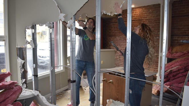Matt Gawors and Jenna Jenks do demolition work at their future Confluence Running Hudson Valley store, at 1 Railroad Ave. in the Village of Goshen, to prepare for their athletic shoe and apparel shop's anticipated opening in mid-May.