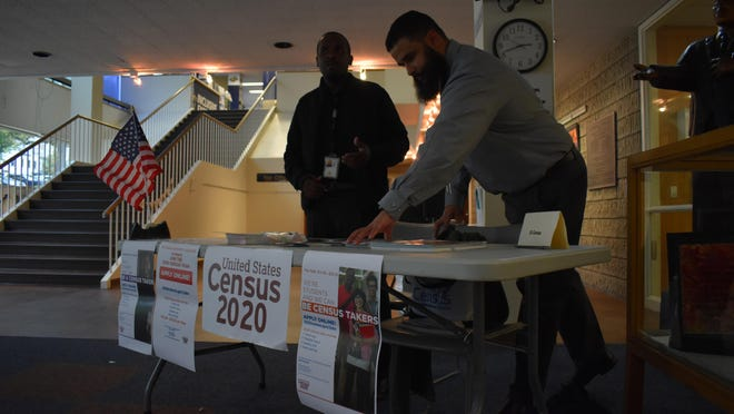 U.S. Census Bureau workers Eric Marion, left, and Mario Garcia arrange 2020 Census pamphlets at a booth near the entrance to the Newburgh Free Library in October. About 30 people applied for jobs to help with the 2020 count during a recruitment event.