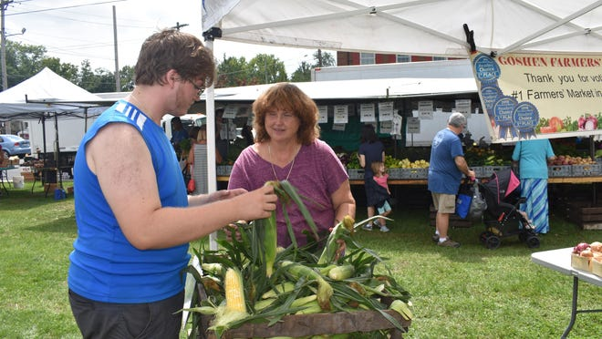Diana Lupinski and her son Andrew sort ears of corn at the Goshen Farmers Market in August 2018. The family runs John Lupinski Farms, one of the founders of the market, in the Town of Goshen. They will not return to the market this year over a disagreement with Goshen Chamber of Commerce Executive Director Barbara Martinez.