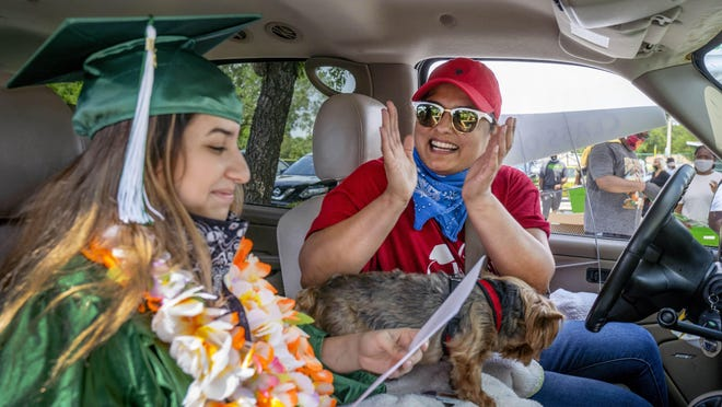 Atlantic High School senior Stephany Morales gets cheers from her mom, Jitza Jimenez after driving through to pick up her diploma in the parking lot at Pompey Park in Delray Beach, Florida on May 27, 2020. Graduates were not allowed to have their normal commencement together because of the coronavirus.