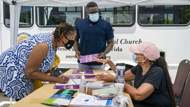 Kamala Golston, left, updates her voter registration with Quincy Bates and Sanjena Clay at the Payne Chapel African Methodist Episcopal Church during a 'Voting is a Vibe' Community Block Party Saturday in West Palm Beach. The event was designed to promote voter registration, early voting, and completing the U.S. Census.