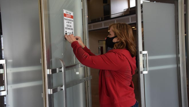 Kelli Cunningham, assistant director of housing and human services, tapes social distancing guidelines on the door at the  shelter at the Houma Municipan Auditorium, in Houma, Louisiana, for Tropical Storm Cristobal.