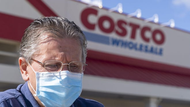Dobro Hajek of Jupiter, wears a mask as he pushes a cart to his car at a Costco store in Palm Beach Gardens earlier this month. People are flocking to stores for food and supplies due to the coronavirus outbreak.