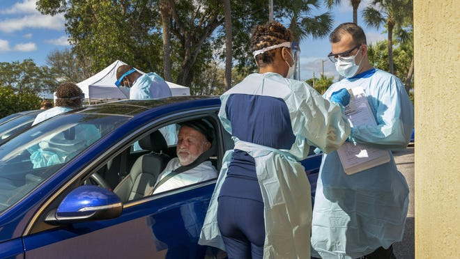 Richard Durant, 68, sits in his car after a being tested Monday by Drs. Oneka Marriott and Alexandru Manning at a drive-thru station at the FoundCare lab in Palm Springs.  Due to overwhelming demand for tests, the lab had to stop taking appointments Tuesday.