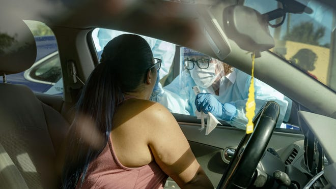 Dr. Leslie Diaz, swabs Yessenia Fonseca for testing for COVID-19 at a drive through station set up in the parking lot of FoundCare, a federally qualified health center in West Palm Beach, Florida on Monday, March, 16, 2020.