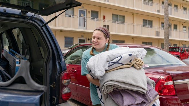 Palm Beach Atlantic University student Bella Langston of Dallas, Texas, carries here bedding to her car after students were asked to go home to help curb the spread of the coronavirus in West Palm Beach, Florida on March 23, 2020.