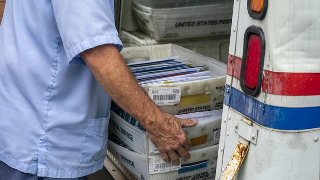 Mail carriers load trucks for deliveries at a U.S. Postal Service facility.