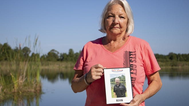 Audrey Jowett holds a picture of her husband, Kevin Jowett, in May. Kevin has been in the United Kingdom for 12 weeks instead of 15 days as he originally planned.