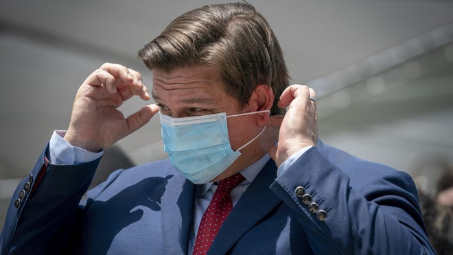Gov. Ron DeSantis puts his mask on after speaking at the Loggerhead Marinelife Center in Juno Beach, Florida on  June 30, 2020. The governor also signed two bills related to protecting the state's environment.