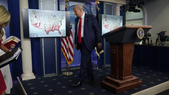 President Donald Trump leaves after speaking at a news conference at the White House, Thursday, July 23, 2020, in Washington. White House press secretary Kayleigh McEnany is at left.