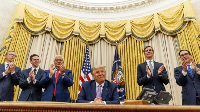President Donald Trump, accompanied by From left, U.S. special envoy for Iran Brian Hook, Avraham Berkowitz, Assistant to the President and Special Representative for International Negotiations, U.S. Ambassador to Israel David Friedman, President Donald Trump's White House senior adviser Jared Kushner, and Treasury Secretary Steven Mnuchin, smiles as he announces that the United Arab Emirates and Israel have agreed to establish full diplomatic ties as part of a deal to halt the annexation of occupied land sought by the Palestinians for their future state.