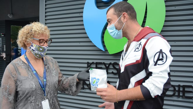 Joan Guadagnino, left, chief operating officer, talks with Aaron Amato, one of the first patients who picked up a supply of medical marijuana Thursday at the first medical marijuana dispensary in Monroe County, located on Route 611 in Stroud Township.