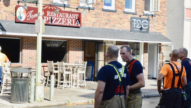 Some of the 50 firefighters from seven fire departments survey the damage Monday morning on Crystal Street in East Stroudsburg outside Tony's Restaurant & Pizzeria.