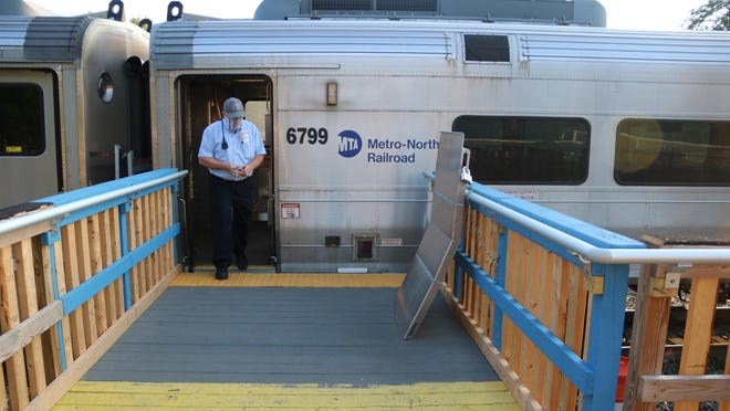 Conductor Steve Burkert steps out at the Port Jervis station where a ramp to close the gap between the train and the platform is locked to the railing.
