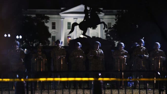 With the White House in the background, a line of police forms behind a fence in Lafayette Park as demonstrators gather to protest the death of George Floyd, Tuesday, June 2, 2020, in Washington. Floyd died after being restrained by Minneapolis police officers.