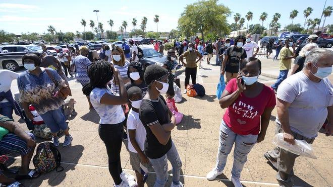 Evacuees wait to board buses Tuesday in Galveston, Texas. The evacuees were being taken to Austin, Texas, as Hurricane Laura headed toward the Gulf Coast.