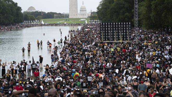 """People gather at Lincoln Memorial to attend the March on Washington, Friday Aug. 28, 2020, on the 57th anniversary of the Rev. Martin Luther King Jr.'s """"I Have A Dream"""" speech."""