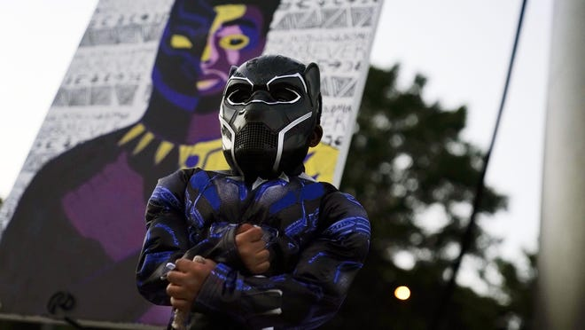 Mason Wilkes, 4, of South Carolina, poses for his father in a Black Panther costume, in front of a paining during a Chadwick Boseman Tribute on Thursday, Sept. 3, 2020, in Anderson, S.C.