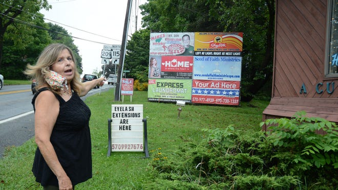 Janice Boyle, owner of A Cut Above Haircutters on Route 209 in Brodheadsville, points to the billboards PennDOT wants moved for its roundabout construction project. Boyle fears the move will cut the income the signs generate as she nears retirement.