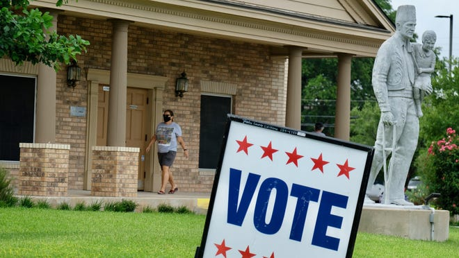 A masked voter at the Ben Hur Shrine Center on June 29 on the first day of early voting in the July runoff elections and the special election for a Central Texas state Senate seat.