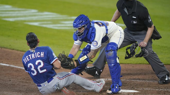 Seattle catcher Joseph Odom tags out Texas' Derek Dietrich as plate umpire Lance Barrett looks on during the seventh inning Sunday.