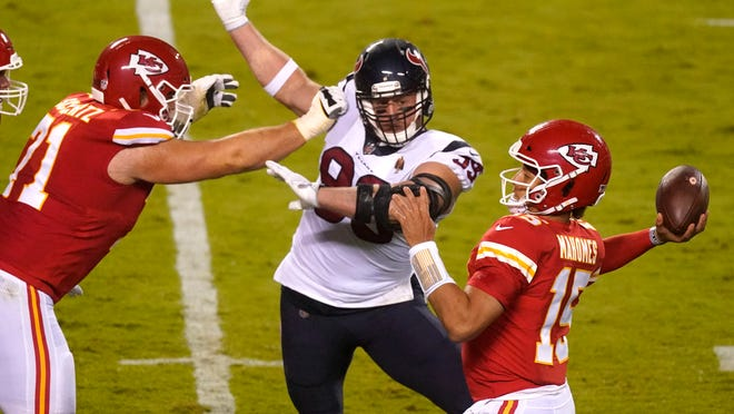 Kansas City Chiefs quarterback Patrick Mahomes (15) passes as he is pressured by Houston Texans defensive end J.J. Watt (99) in the first half of an NFL football game Thursday, Sept. 10, 2020, in Kansas City, Mo.
