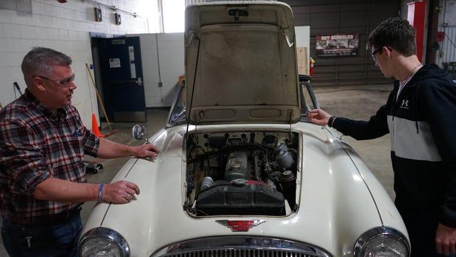 Frenship High School automotive teacher Dana Vinson works on a project with a student.
